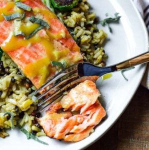 A fork cutting into sous vide salmon on a bed of rice.