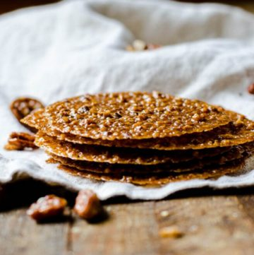 A stack of pecan lace cookies surrounded by candied pecans.