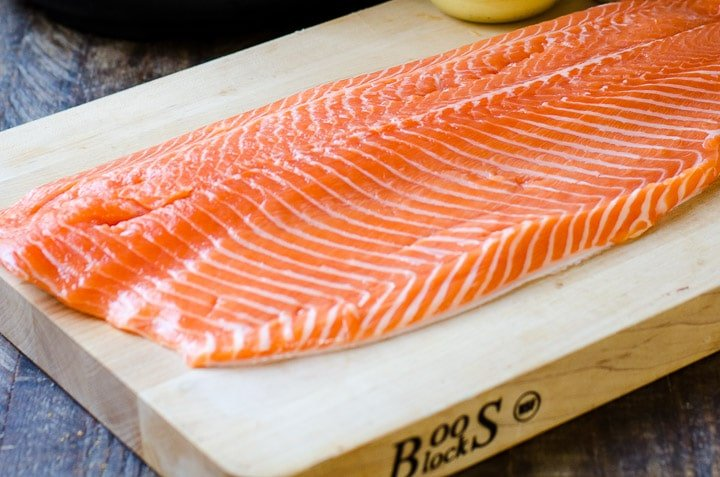 A whole salmon fillet on a wooden cutting board.