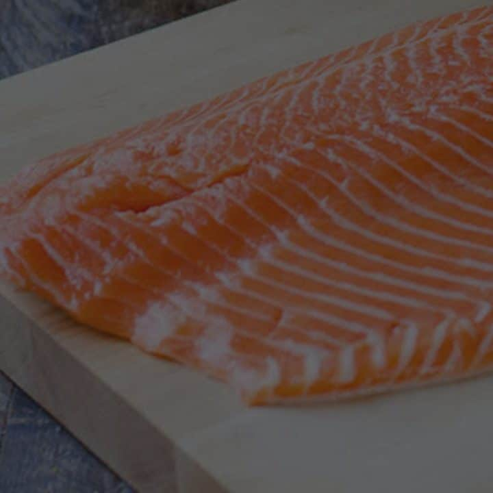 Black overlay on a side of salmon on a wooden cutting board.
