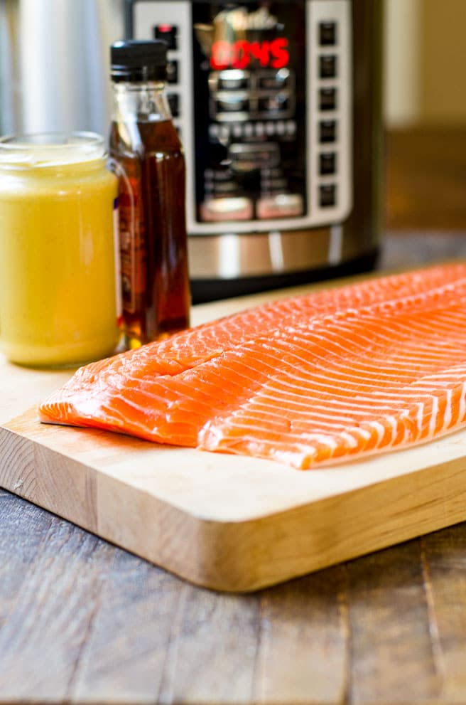 A whole salmon fillet on a cutting board.