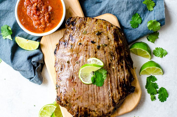 A two pound broiled flank steak on a cutting board.