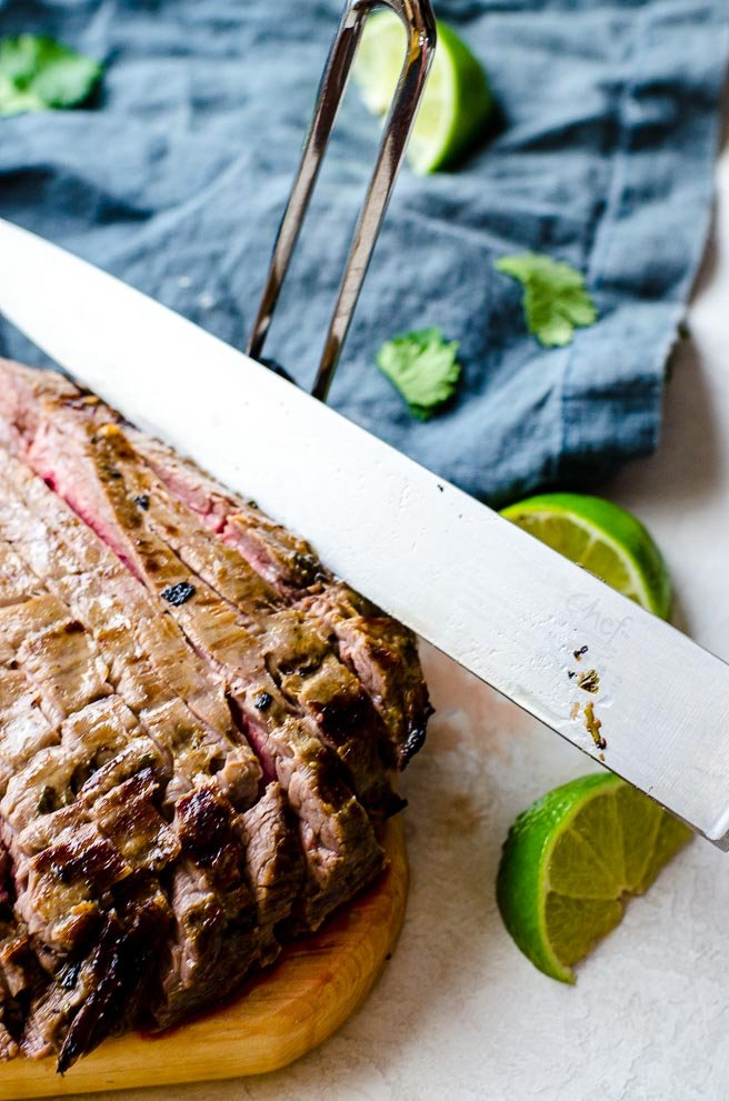 A knife slicing into flank steak showing the angle to cut to get it thin.