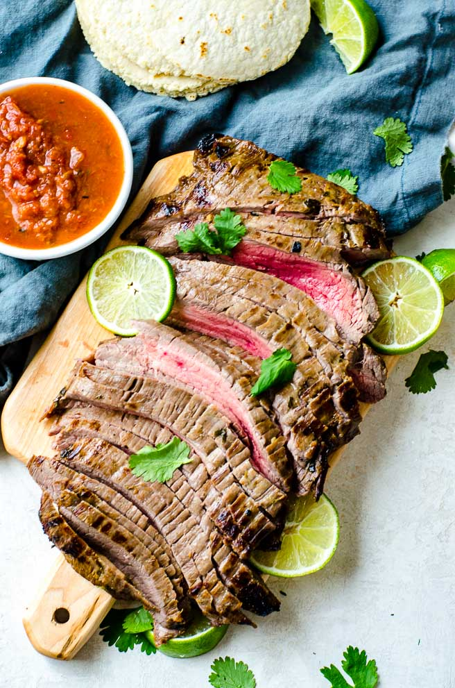 Overhead view of carne asada meat on a cutting board.