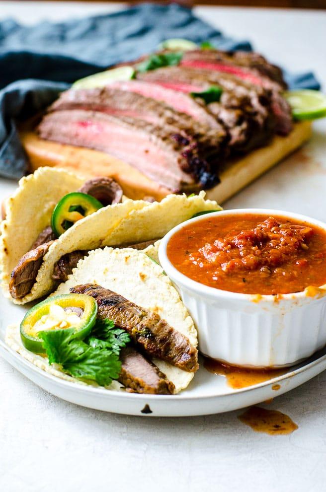 A plate of carne asada tacos next to a bowl of salsa.