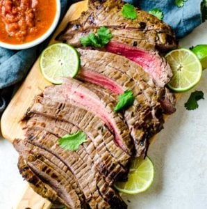 Sliced carne asada meat on a cutting board. It is cooked to medium rare.