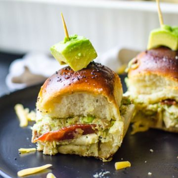 A hawaiian roll turkey slider with a toothpick in the middle on a black plate.