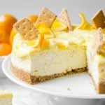 Creamy lemon curd dripping off the side of a meyer lemon cheesecake that is sliced.