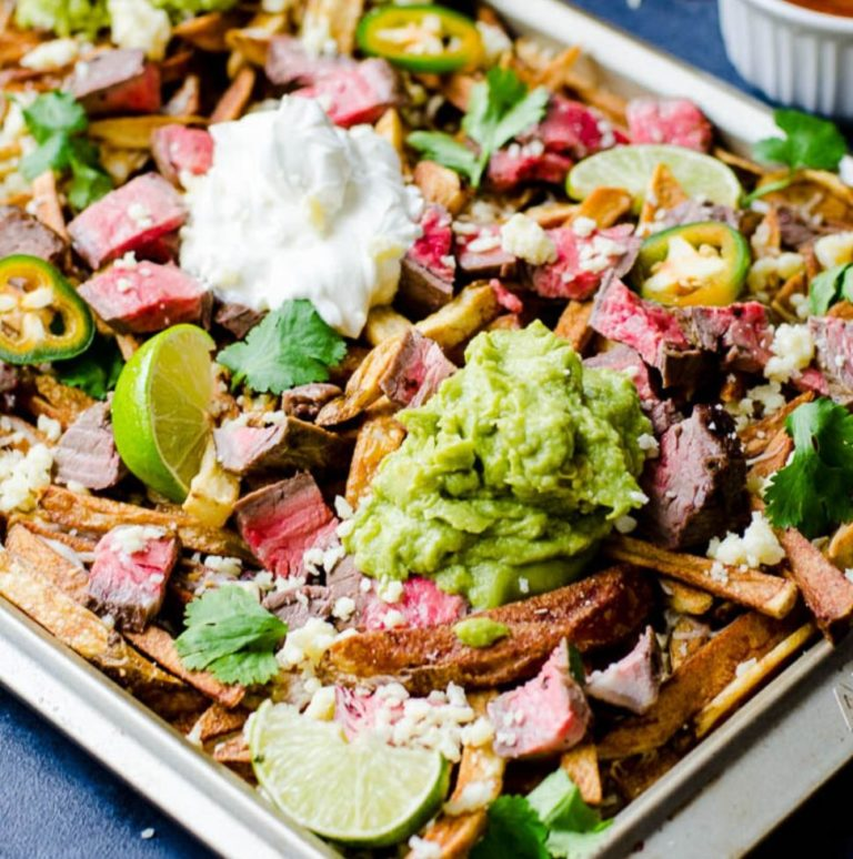 Perfect for game day, these crispy french fries are topped with melted cheese, sour cream, guacamole, and smoky carne asada meat.