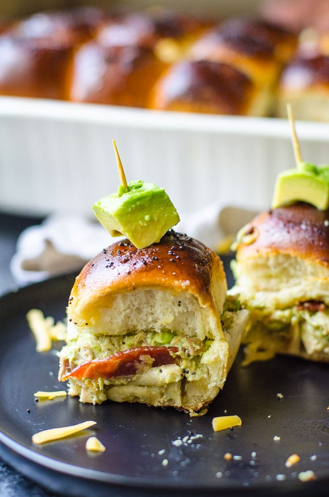 A cube of avocado garnishes turkey sliders on a black plate.