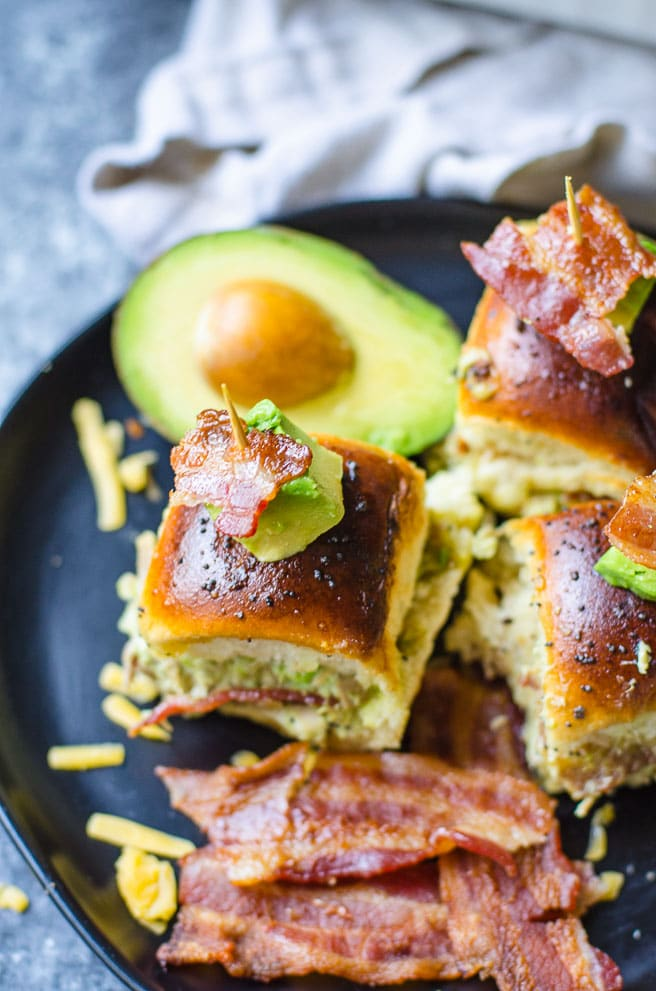 A black plate filled hawaiian roll turkey sliders, cooked bacon, and avocado.