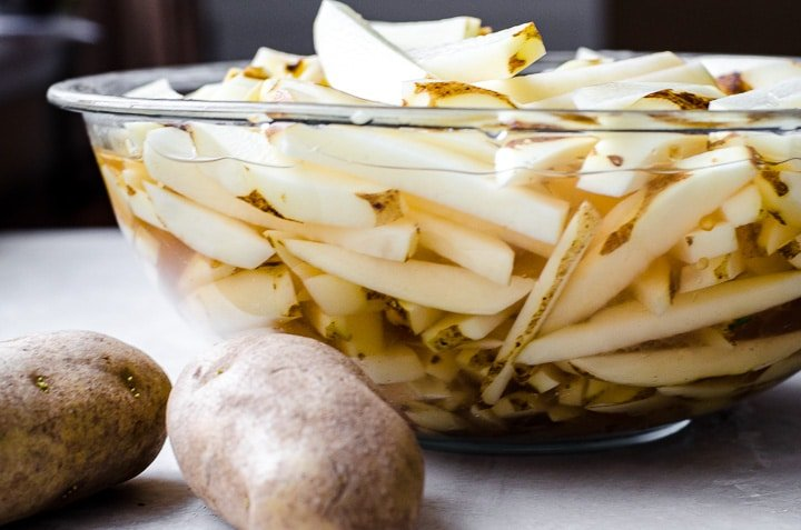Cut potatoes soaking in a bowl before frying into french fries.