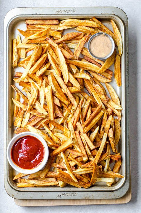 Overhead view of a baking sheet of homemade french fries and dipping sauces.
