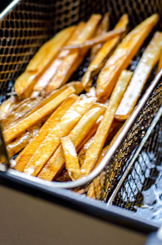 A deep fryer basket pulling out freshly fried fries.