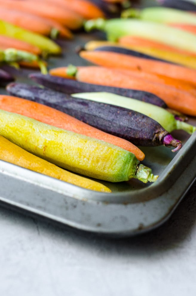 Peeled rainbow carrots on a sheet pan before roasting.