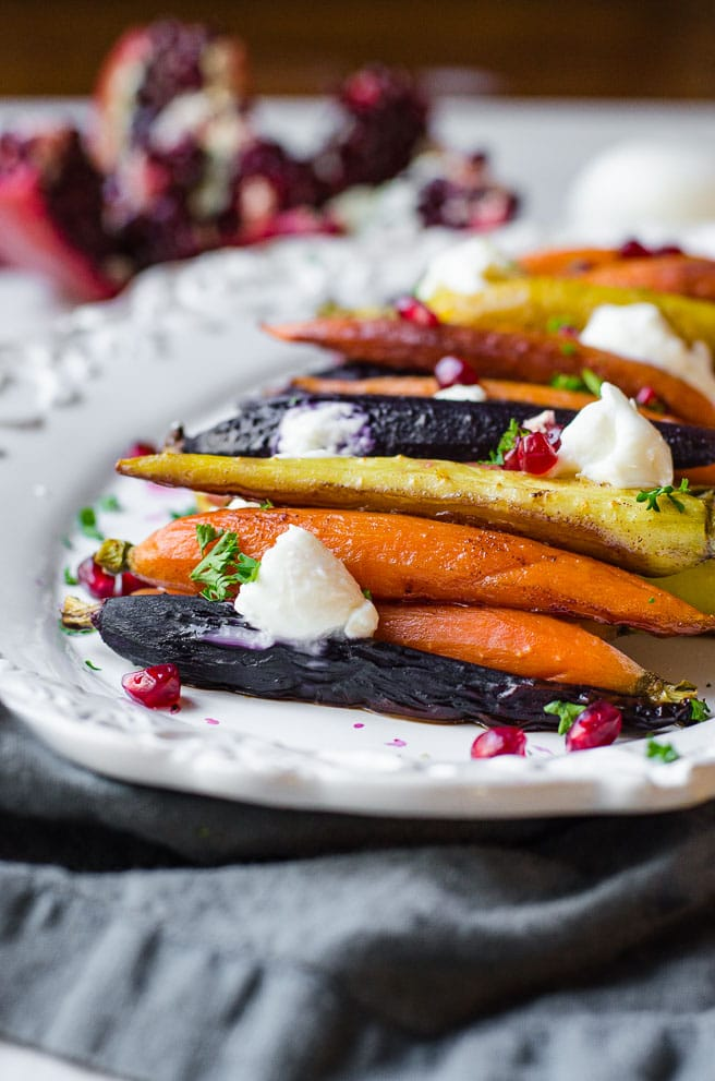 A white platter of roasted rainbow carrots garnished with burrata and pomegranate seeds.