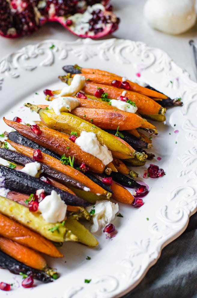 Buratta cheese and pomegranate decorating a white platter of carrots.