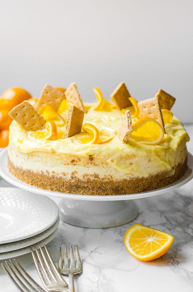 A whole Meyer lemon cheesecake on a serving stand ready to serve.
