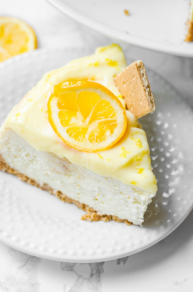 A single slice of lemon cheesecake on a plate. It is garnished with a lemon wheel and graham cracker.