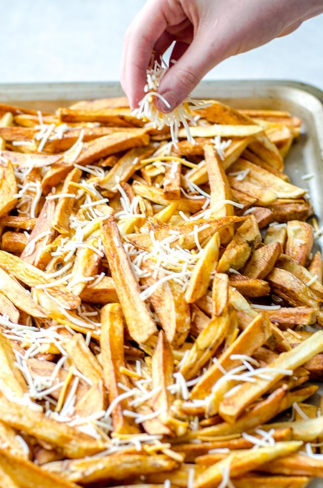 A hand sprinkling cheese onto french fries.