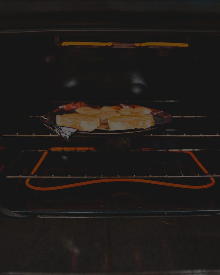 Black overlay on a pan of bread toasting under a broiler.