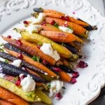 A white platter with rainbow honey roasted carrots lined up.