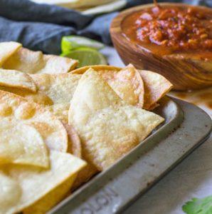 Homemade tortilla chips on a pan next to salsa.