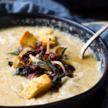 Close up of the bacon and caramelized onion garnish in a bowl of roasted cauliflower soup.