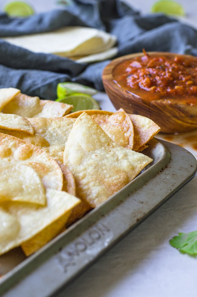 A sheet pan of tortilla chips by limes and salsa.