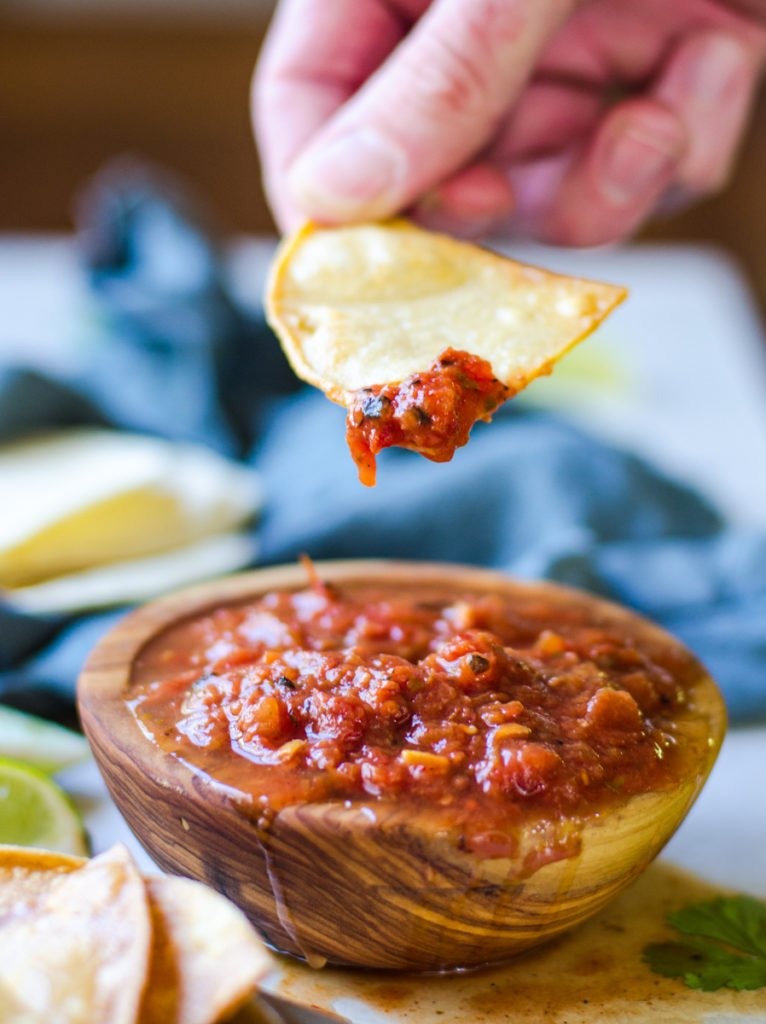 A hand holding a tortilla chip pulling salsa out of a bowl