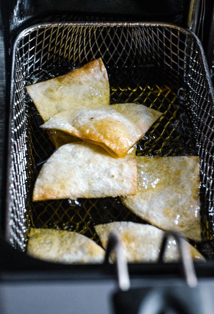 Tortillas frying in a deep fryer basket.