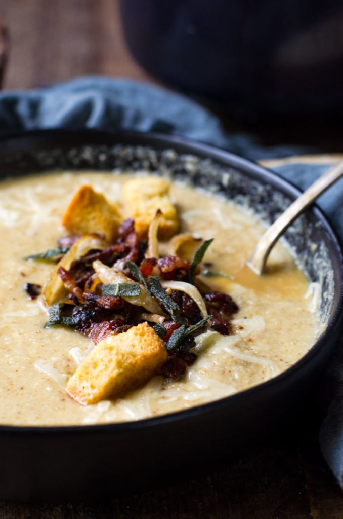 A black bowl of roasted cauliflower soup with bacon and croutons.