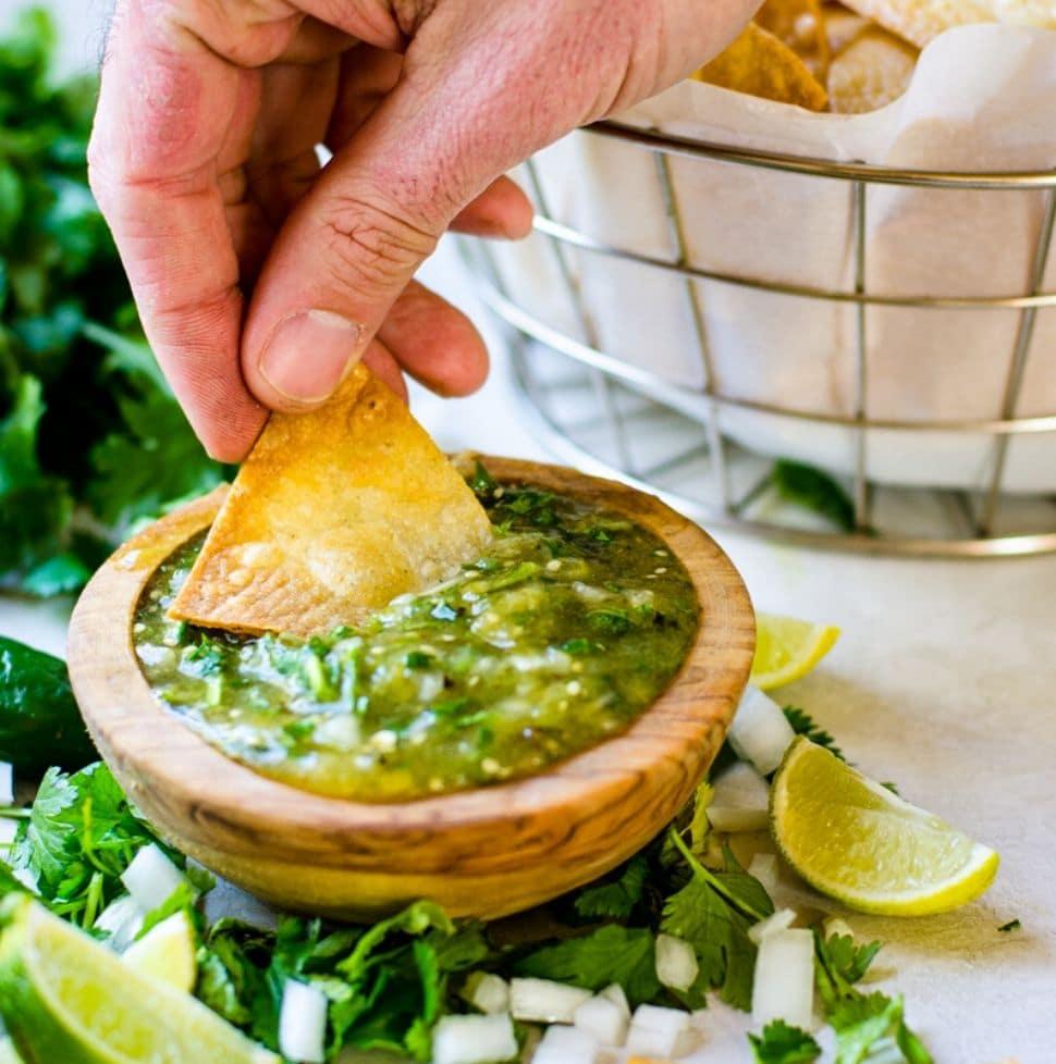 A hand dipping a tortilla chip into tomatillo salsa.