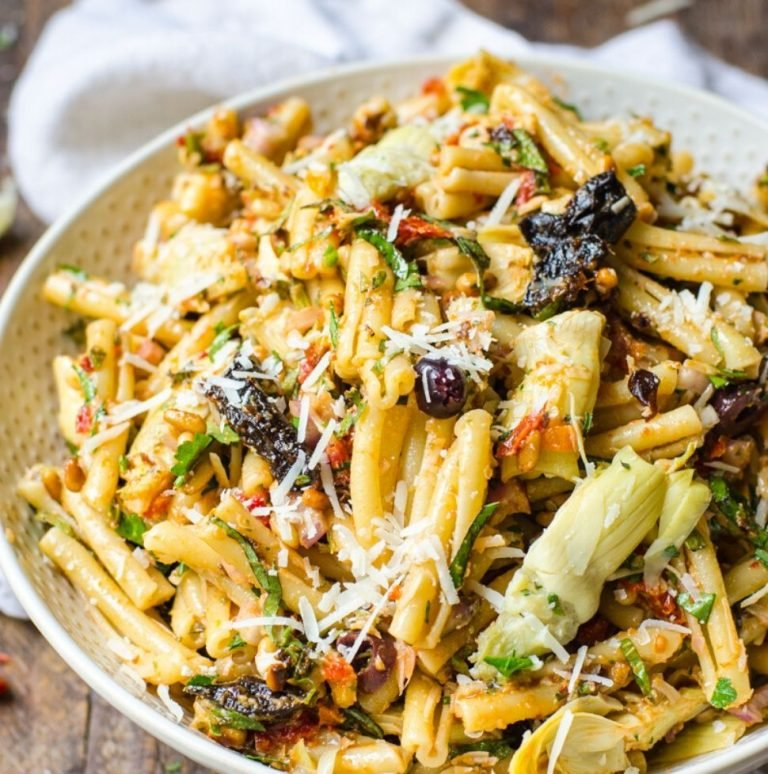 A large bowl of sun dried tomato pasta salad with California prunes garnished with cheese.
