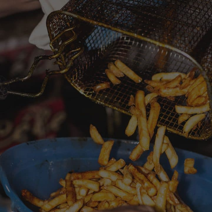 Black overlay on a deep frying basket putting french fries in a bowl.