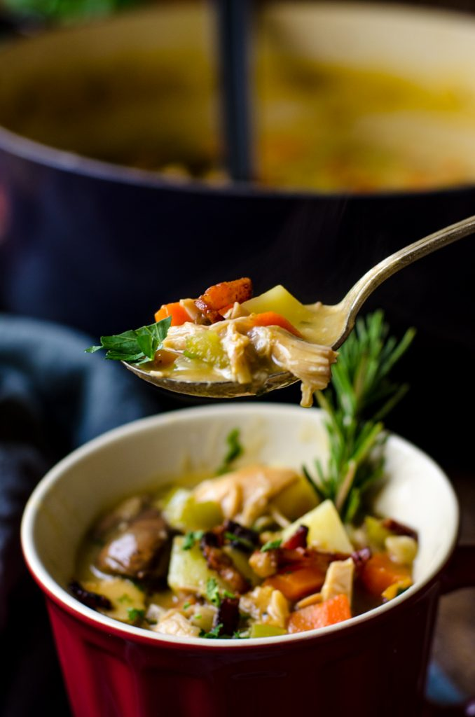 A spoon lifting leftover turkey soup out of a bowl.