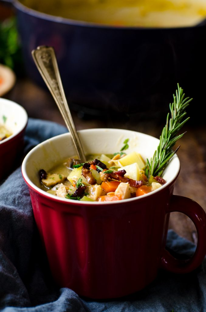 A red soup mug of soup with a spoon and rosemary garnish.