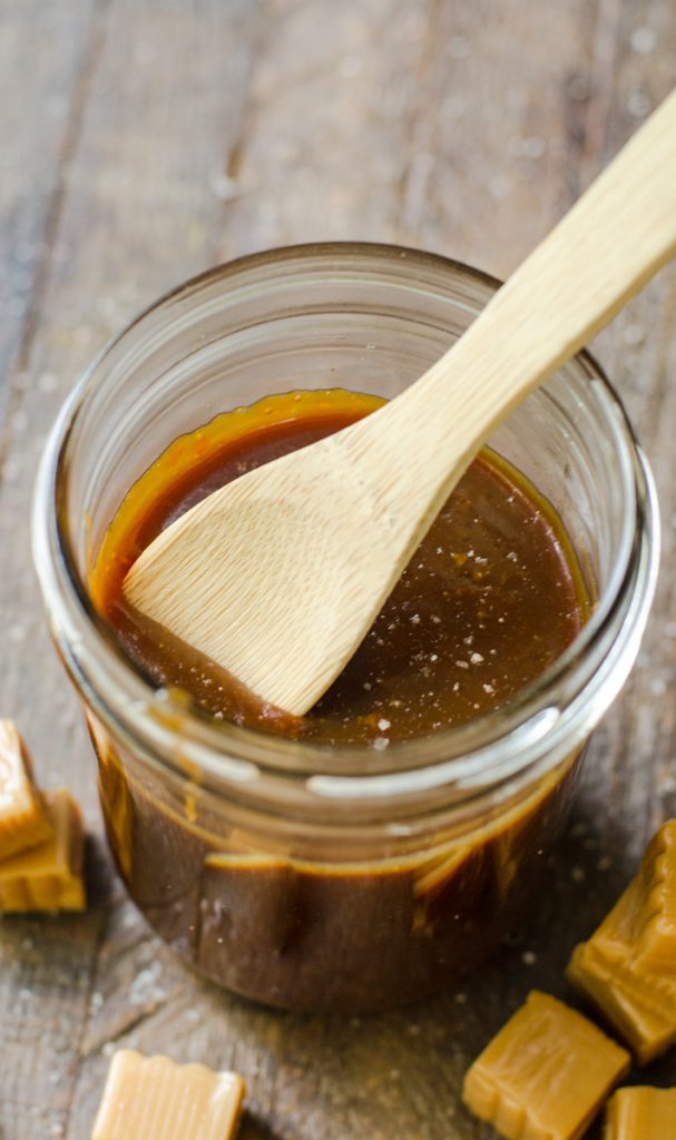 A wooden spoon scooping up caramel sauce from a jar.
