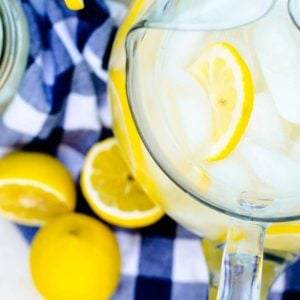 Overhead view of a pitcher of reconstituted frozen lemonade concentrate on a blue checkered napkin.