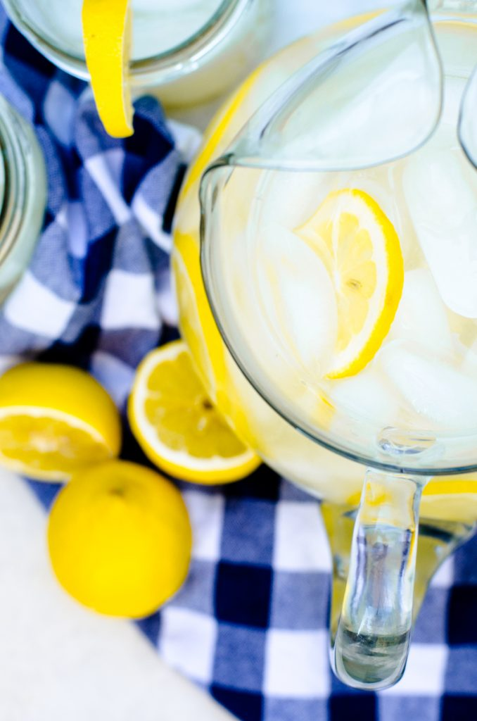 A pitcher of lemonade concentrate with fresh lemons in it.