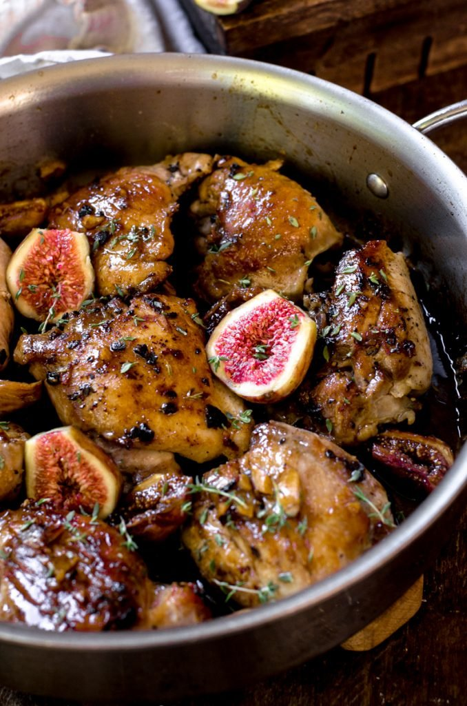 Cooked chicken thighs in a pan with fresh halved figs between them.