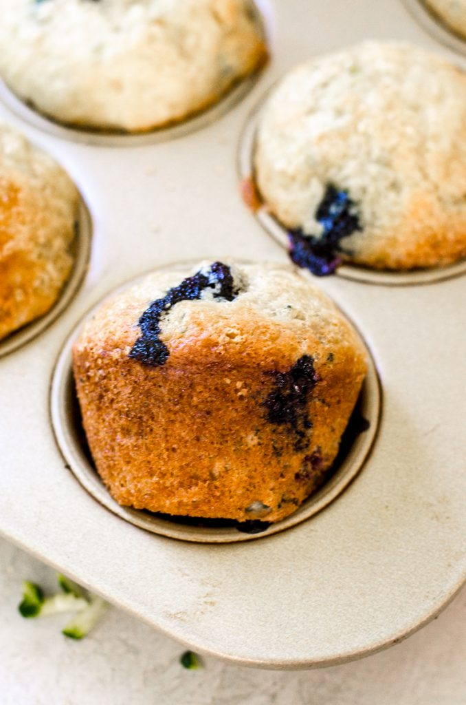 A blueberry muffin turned sideways in a muffin pan.