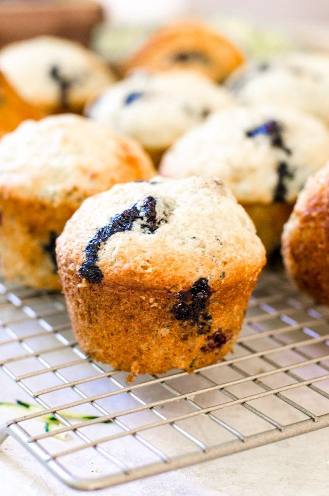 Close up of blueberry zucchini muffins on a cooling rack.