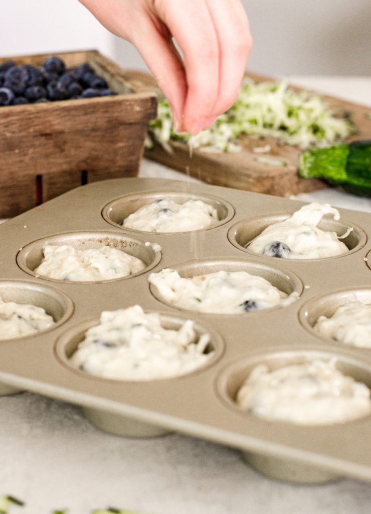 A hand sprinkling sugar in the raw over muffin batter.