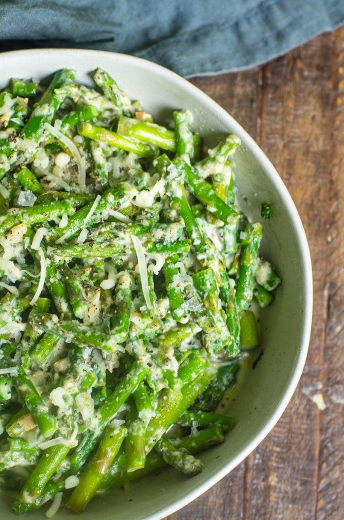 A bowl of cut asparagus in a cream sauce.