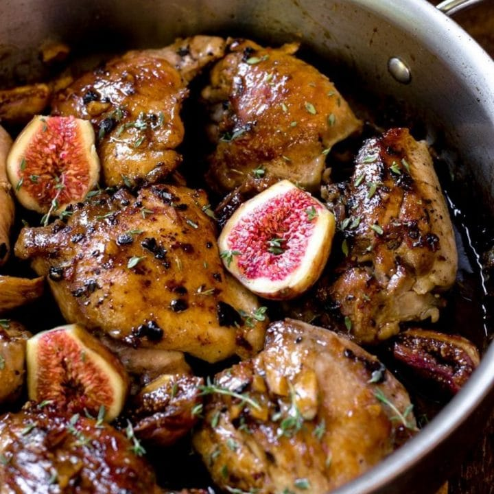 A pan of cooked chicken thighs with fresh figs.