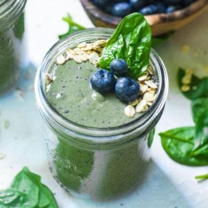 blueberries, spinach, and oats on top of a smoothie in a mason jar.