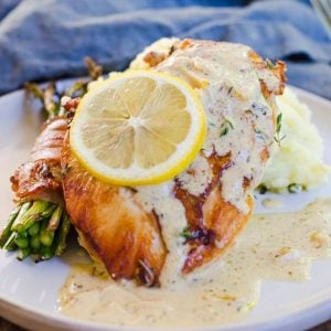 A lemon wheel garnishes herbs de provence chicken on a gray plate with sauce.