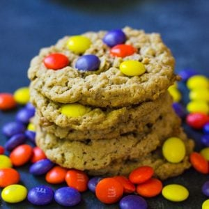 A stack of hocus pocus cookies surrounded by purple, yellow, and orange m&M's.