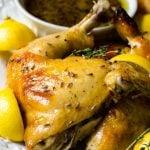 lemon wedges next to a lavender chicken leg quarter on a serving platter.